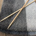 Knitted scarf with knitting needles.