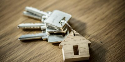 Keychain with keys and a wooden house.